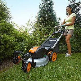 Woman using a corded mower in the yard