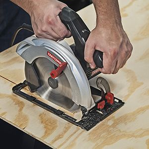 Corded circular saw being guided through lumber