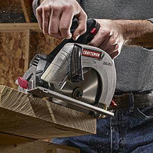 Cordless circular saw being guided through lumber