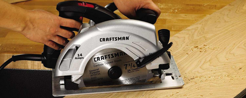 Hands guiding circular saw through board