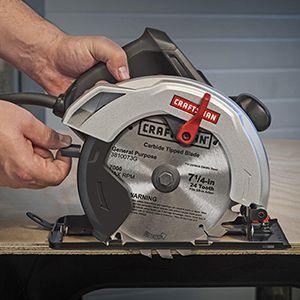 Hand adjusting blade guard on circular saw