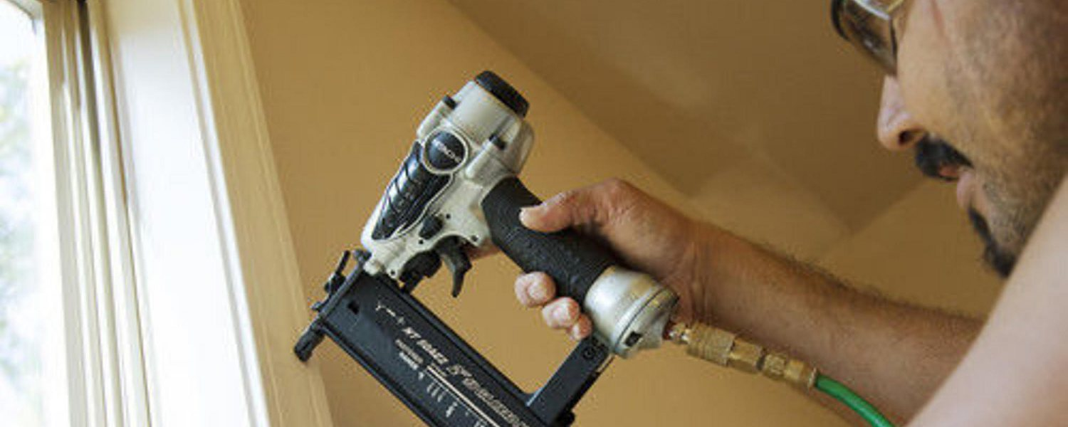 Man using a brad nailer to secure trim