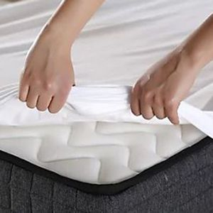 Fitted Sheets Being Put on a Bed