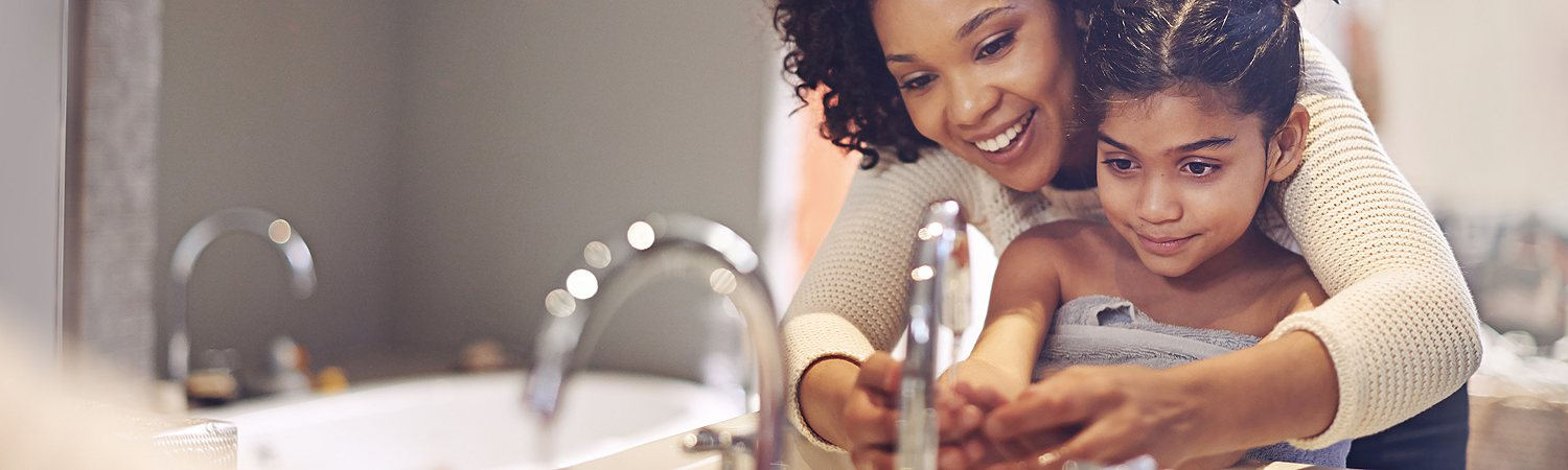 Mom and Daughter Washing Hands at Bathroom Faucet
