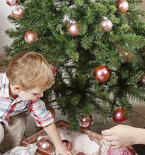 Young boy putting ornaments on a tree