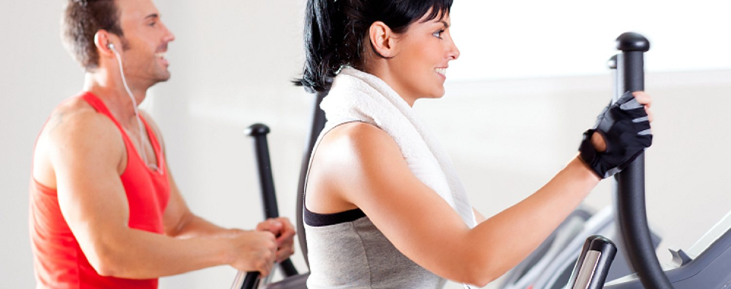 Woman and man on elliptical trainers