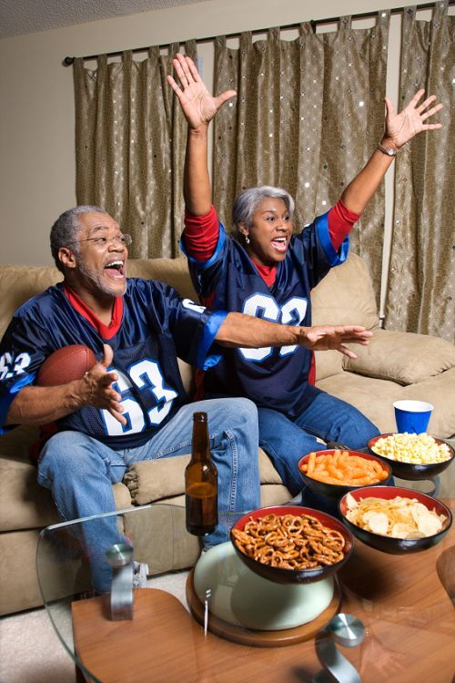 Couple watching football with snacks