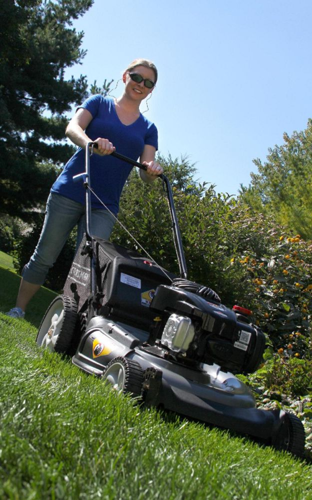 Woman mowing the lawn with a push mower