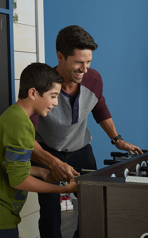 Father and son teaming up at foosball