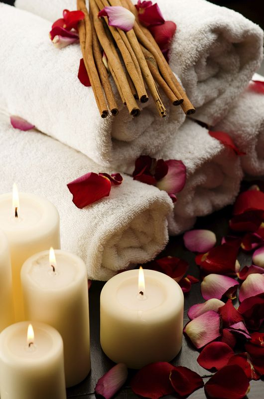 Scented candles, towels and rose pedals