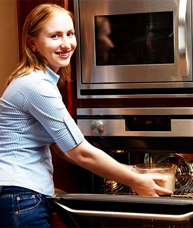 Woman using a wall oven