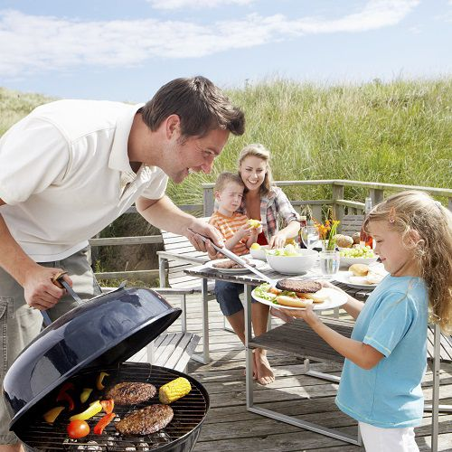 Dad and daughter cooking on the grill