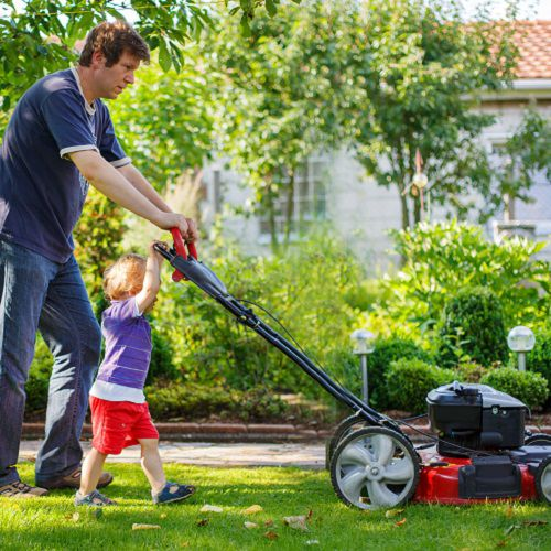 Dad and son mowing the lawn