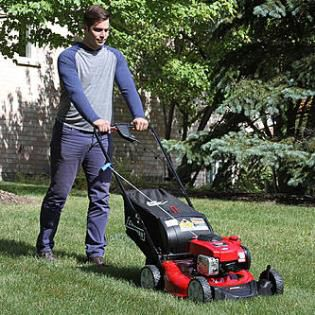 Man using a gas mower in yard